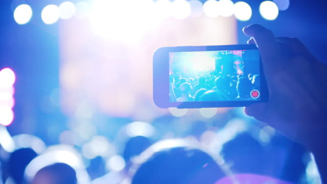 Fan recording a video in a concert