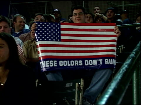 fan sitting in bleachers holds up american flag poster these colors don't run at shea stadium at first mlb baseball game after september 11 terrorist... - atlanta braves stock-videos und b-roll-filmmaterial