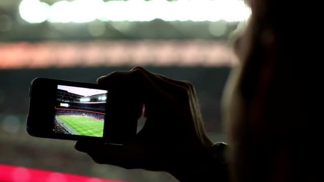 Fan Taking a Photo in the Sports Stadium / Arena