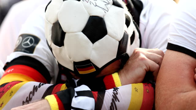 A fan with a football as cap is seriously disappointed and cannot believe that Germany is loosing the 2018 FIFA World Cup Russia Group F match...