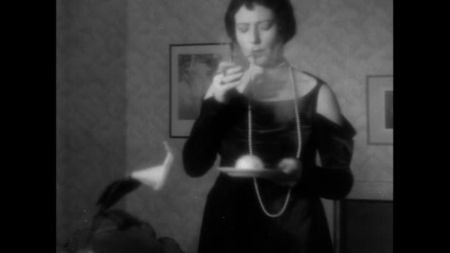 "stockvideo's en b-roll-footage met montage fancily dressed housewife in house called ""kismet,"" smoking, lounging, and pushing a white cat off a chair / england, united kingdom - 1930"