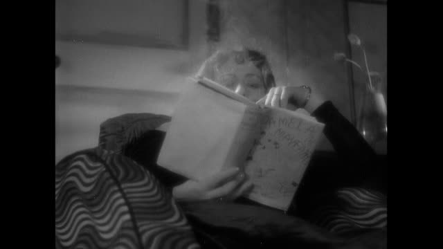 vídeos de stock, filmes e b-roll de montage fancily dressed housewife reading trashy novel while blowing smoke from a long cigarette holder and white cat ducks around her ankles / england, united kingdom - cigarro