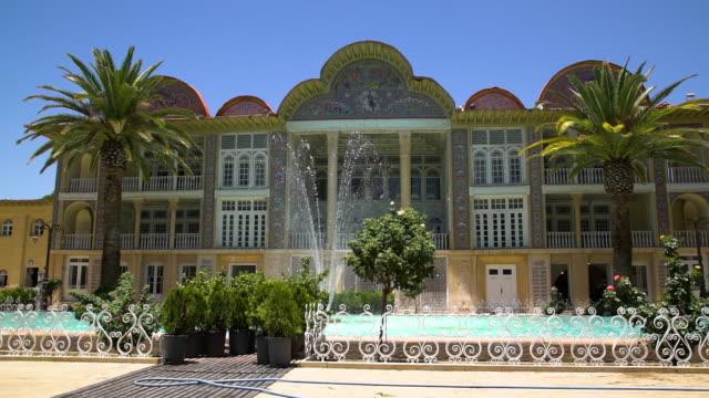 vídeos de stock, filmes e b-roll de a fancy curved mosaic building with a water fountain and palm trees - armação de janela