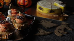 Fancy Halloween food Party Table with Pumpkin Cupcake Muffin and cookies.
