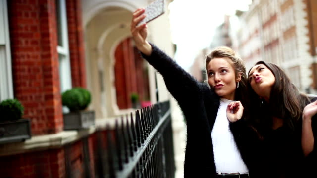 Fancy women in London selfie with mobile phone