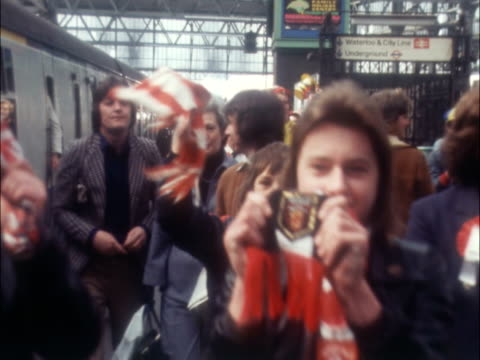 stockvideo's en b-roll-footage met fans arrive in london for fa cup final 1976 england london southampton plans on train platform with banners and favours fans walk towards camera... - southampton engeland