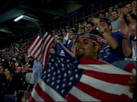 ws fans at shea stadium sitting in bleachers smiling waving american flags shouting lets go mets man w/ us flag bandanna on head holding flag in fg... - shea stadium stock videos and b-roll footage