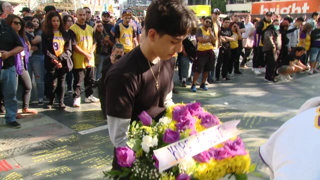 vidéos et rushes de fans bring flowers at crowds gather outside staples center for kobe bryant memorial at staples center on january 27, 2020 in los angeles, california. - mémorial