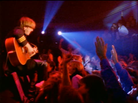 pan fans cheering for electric guitarist performing on stage in rock concert - moderne rockmusik stock-videos und b-roll-filmmaterial