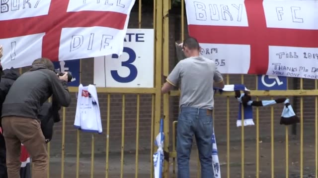 stockvideo's en b-roll-footage met fans gather and leave tributes at gigg lane following bury's expulsion from the english football league. fans can be seen waiting around the stadium,... - english football association