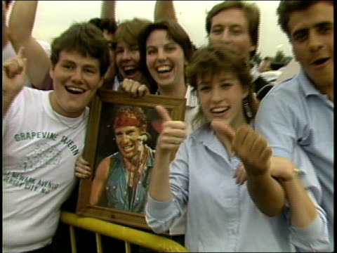 fans holding framed picture of bruce springsteen and chanting his name - 1985年点の映像素材/bロール