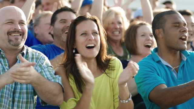 Spectators cheer at a sporting event.