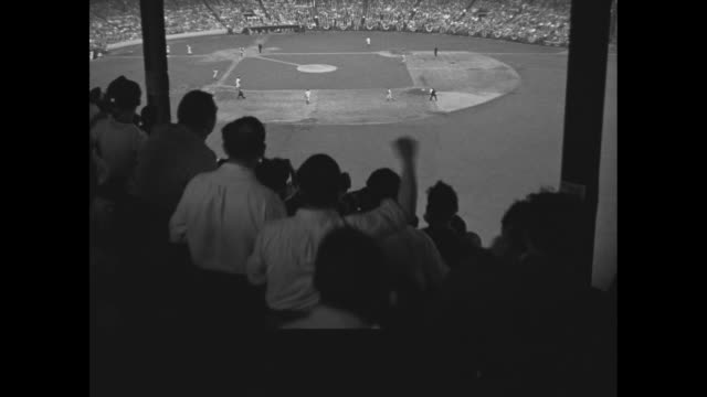 Fans in stands at the Polo Grounds / Morton Cooper of the St Louis Cardinals pitches for the National League team during the AllStar Game in New York...