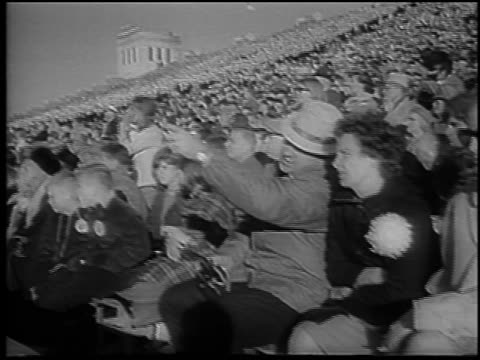 B/W 1965 fans in stands pointing rising at Army vs Navy football game / Philadelphia / newsreel