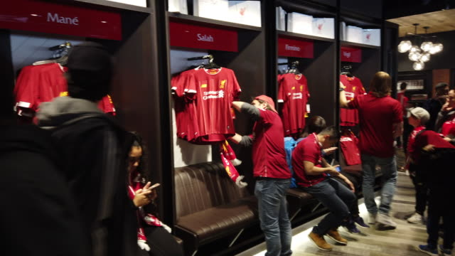 vídeos de stock e filmes b-roll de fans looking at replica shorts in the club shop before liverpool's final premier league match of the season against wolverhampton wanderers on may... - liverpool inglaterra