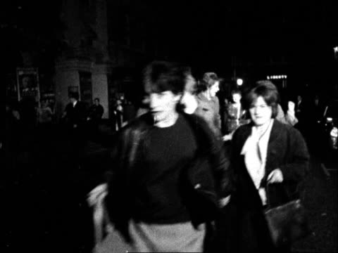 fans mob the beatles as they leave the palladium; england: london: the palladium: ext / night the beatles running - john lennon, paul mccartney,... - the beatles stock videos & royalty-free footage