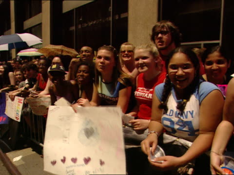 fans, mostly teenage girls, w/ homemade signs, standing behind barricade on sidewalk, screaming it's magical! - barricade stock videos & royalty-free footage