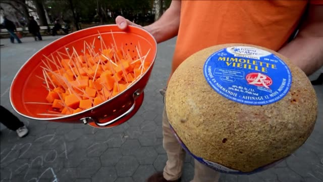 fans of the french cheese mimolette which was banned by the us food and drug administration because of cheese mites on its surface hand out samples... - french food stock videos & royalty-free footage