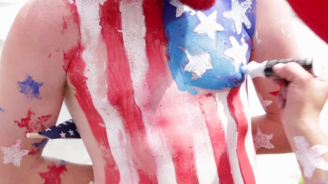 s fans paint us flags on their bodies prior to a viewing party of the world cup united states vs belgium match at the freedom plaza washington dc... - body paint stock videos & royalty-free footage