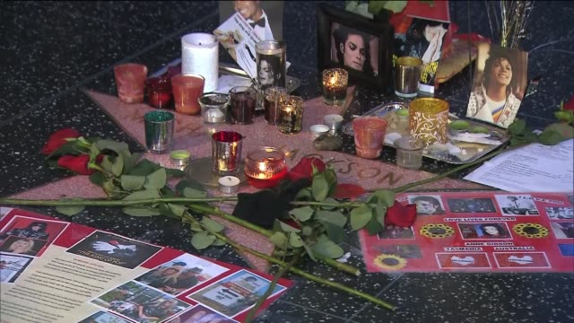 vídeos de stock e filmes b-roll de fans placed pictures, candles, and memorabilia on michael jackson's star on the 5th anniversary of his death. ktla - morte