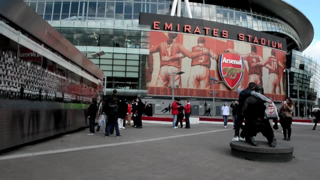 Fans posing next to the statue of Thierry Henry at The Emirates Stadium home to Arsenal Football Club in north London February 7 2013 General View Of...