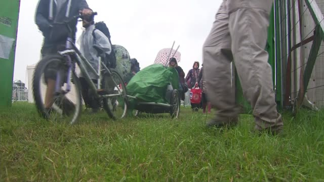 fans queue for hours to get in to glastonbury festival; tractor towing car with caravan through muddy field on site women in wellington boots along... - festival goer stock videos & royalty-free footage
