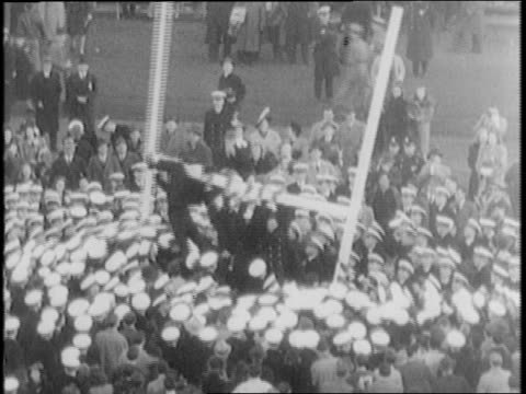 vidéos et rushes de fans rush onto field and tear down goal post / fans and players snap to attention on field and in stands for star spangled banner / sailors tear down... - 1941