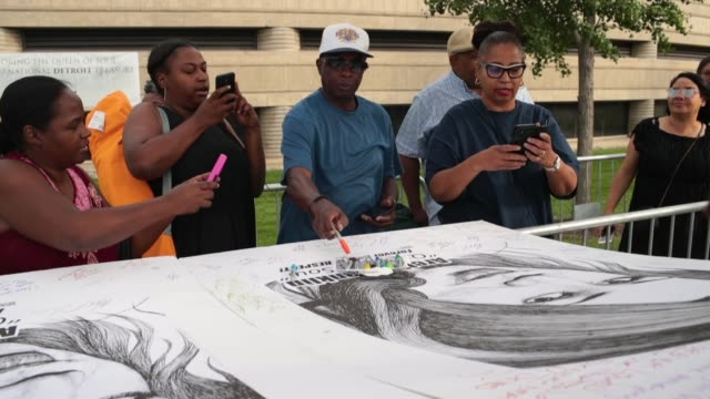 Fans sign posters of Aretha Franklin created by artist Mark Gaines outside of the Charles H Wright Museum of AfricanAmerican History where the Queen...