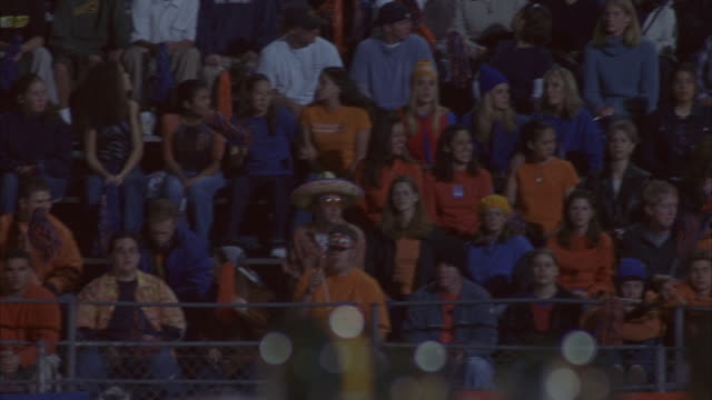 fans sit in the stands at a football game. - rivalry stock videos & royalty-free footage