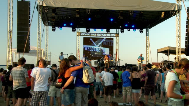Fans watch a rock band perform in front of a video screen onstage at an outdoor concert.