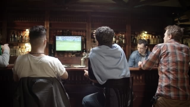 fans watching soccer in sports bar - attività del fine settimana video stock e b–roll