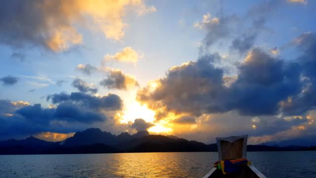 vídeos de stock e filmes b-roll de fantastic landscape stone mountain rang with sunset, boat floating on water - mar de andamão