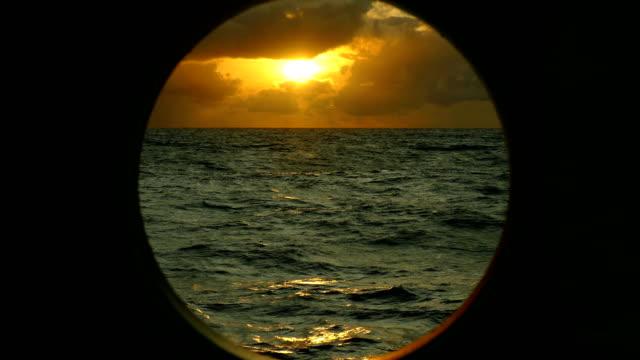 vidéos et rushes de coucher de soleil fantastique dans l'océan atlantique à travers le hublot d'un navire - hublot