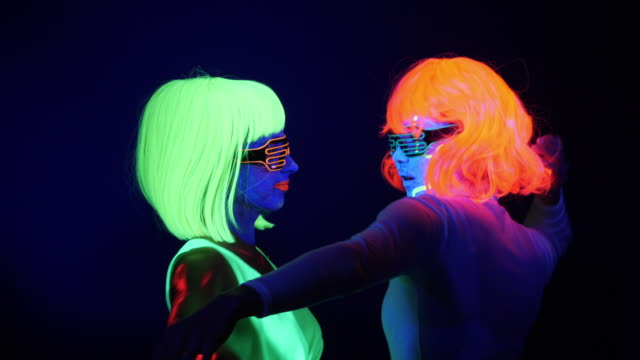fantastic video of sexy cyber raver woman filmed in fluorescent clothing under uv black light.two sexy cyber glow raver women filmed in fluorescent clothing under uv black light - neon stock videos & royalty-free footage