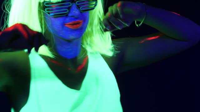 セクシーなサイバー遊び人女の幻想的な映像は、uv ブラック ライト下で蛍光服で撮影しました。セクシーな女の子サイバー グロー uv ブラック ライト、党概念下で蛍光の洋服で撮影レイヴァ - 人体点の映像素材/bロール