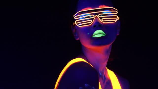 fantastisches video sexy cyber raver frau gefilmt in fluoreszierende kleidung unter uv-schwarzlicht. sexy mädchen cyber leuchten raver frauen gefilmt in fluoreszierende kleidung unter uv-schwarzlicht, party konzept - chinesischer abstammung stock-videos und b-roll-filmmaterial