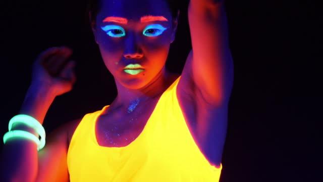 vídeos de stock, filmes e b-roll de vídeo fantástico de mulher de raver sexy cyber filmado em roupa fluorescente luz negra uv. cyber girl sexy brilho mulheres raver filmadas em roupa fluorescente sob luz negra de uv, conceito de festa - néon