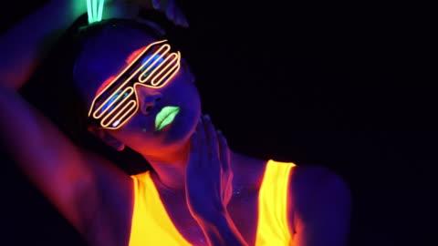 vídeos de stock, filmes e b-roll de vídeo fantástico de mulher de raver sexy cyber filmado em roupa fluorescente luz negra uv. cyber girl sexy brilho mulheres raver filmadas em roupa fluorescente sob luz negra de uv, conceito de festa - discoteca