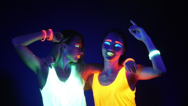 セクシーなサイバー遊び人女の幻想的な映像は、uv ブラック ライト下で蛍光服で撮影しました。2 つのセクシーなサイバー グロー レイヴァー女性 uv ブラック ライト、党概念の下の蛍光服で - 発光色点の映像素材/bロール