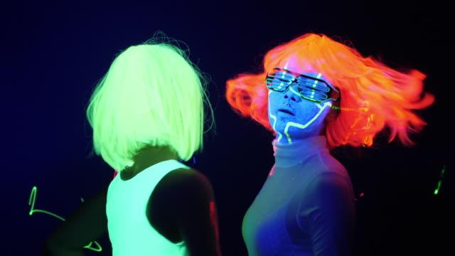 vidéos et rushes de fantastique vidéo de sexy cyber raver femme filmé dans des vêtements fluorescents sous lumière noire uv. fille sexy cyber glow femmes raver filmées dans des vêtements fluorescents sous lumière uv noir, notion de parti - plaisir