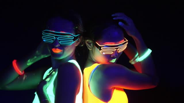 セクシーなサイバー遊び人女の幻想的な映像は、uv ブラック ライト下で蛍光服で撮影しました。セクシーな女の子サイバー グロー uv ブラック ライト、党概念下で蛍光の洋服で撮影レイヴァ - 発光色点の映像素材/bロール
