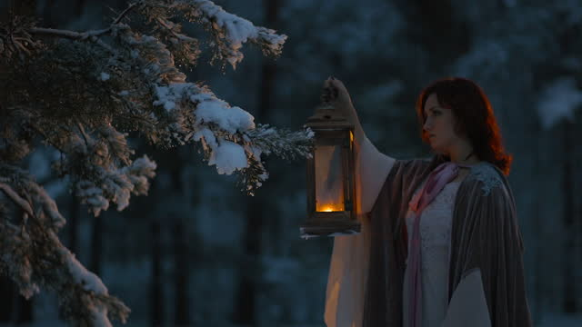 fantasy: young woman holds vintage lantern lighting fir tree covered in snow. medieval fairytale cosplay concept - dark stock videos & royalty-free footage