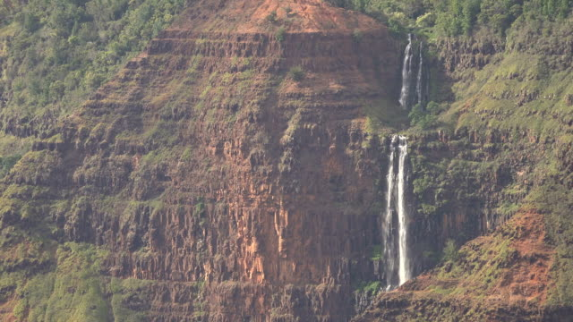 far away waterfalls on edge of kauai island ravine - butte rocky outcrop stock videos & royalty-free footage