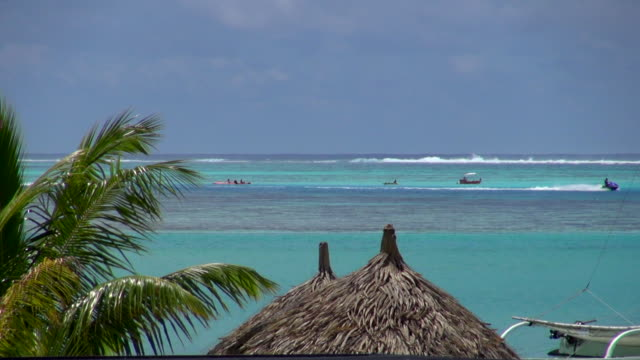 far view of jet skiing on the ocean - insel tahiti stock-videos und b-roll-filmmaterial