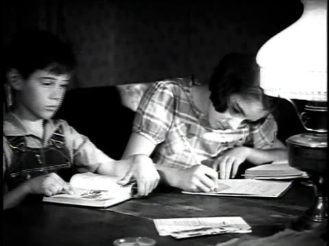 1923 MS Farm children doing their homework by lamplight / United States