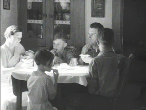 farm family of six at table ms child eating slice of bread w/ thick spread ws president franklin d roosevelt standing w/ son james on back of... - 1934 stock videos & royalty-free footage