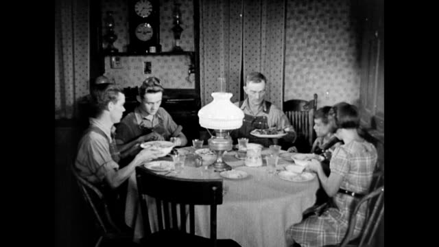 Farm family sits down to dinner / family eats quietly by lamp light / Bill Parkinson and kids leave the table and Hazel Parkinson finishes alone...
