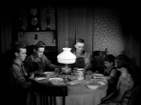 1923 ws farm family sitting down and eating meal at table / united states - 1923 stock videos & royalty-free footage