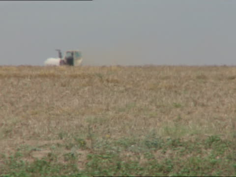 stockvideo's en b-roll-footage met farm land w/ farmer on small tractor moving across brown field little green fg, heatwaves causing distortion ripples, second tractor following same... - agrarisch beroep