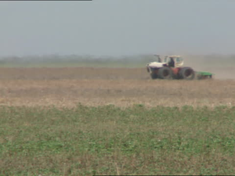 stockvideo's en b-roll-footage met farm land w/ farmer on small tractor moving across brown field some green fg, heatwaves causing distortion ripples on tractor. hot weather, heat,... - southwest usa